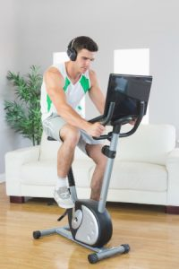 Man doing workout on exercise bike, with laptop.