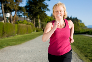 Mature woman running along path in green area