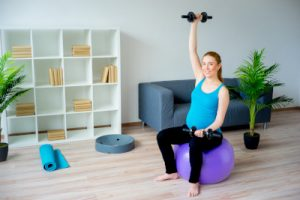 Pregnant woman sitting on a gym ball.