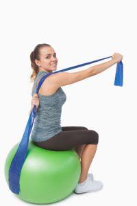Woman sitting on a gym ball using a resitance band.